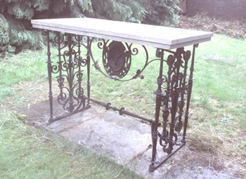 An unusual stone and wrought iron table with cast iron medallion by Morgan, Macaulay and Wade